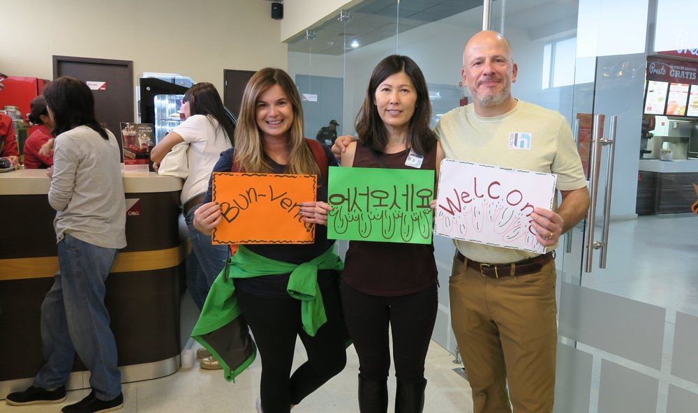 Naomi, Eunjoo and Robert arriving in Valledupar and holding the signs made by Funcovulc saying 'Welcome!'