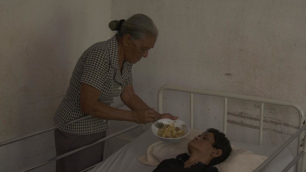 Dilia feeds one of her daughters affected by HD
