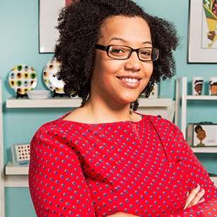 "What started as a creative outlet while earning her mechanical engineering degree is a now full-time venture for Portland native Kayin Talton Davis. Her business, Soapbox Theory, sells cards, tote bags, pillows, T-shirts, and much more, all adorned with Talton Davis' illustrations of Black community—art that she first started drawing in the margins of her class notes.  Talton Davis recalls that as she was growing up there were not a lot of people who looked like her in the books she read in school, and images in the media. So she began creating her own representations. That same passion to represent the under-represented started Talton Davis on the path to engineering. On a field trip in middle school Talton Davis met a woman who was a mechanical engineer designing children's prosthetics. She was immediately inspired. ""I knew I wanted to create something that was positive, helpful and accessible to all.""  Standing among her colorful creations she looks proud, accomplished, and at home. ""It is incredibly fun seeing kids react to my artwork,"" she says. ""The moment they say, 'he/she looks like me!' is when it is reaffirmed that I am doing the right thing.""  Kayin is a 2017 winner of PitchBlack."