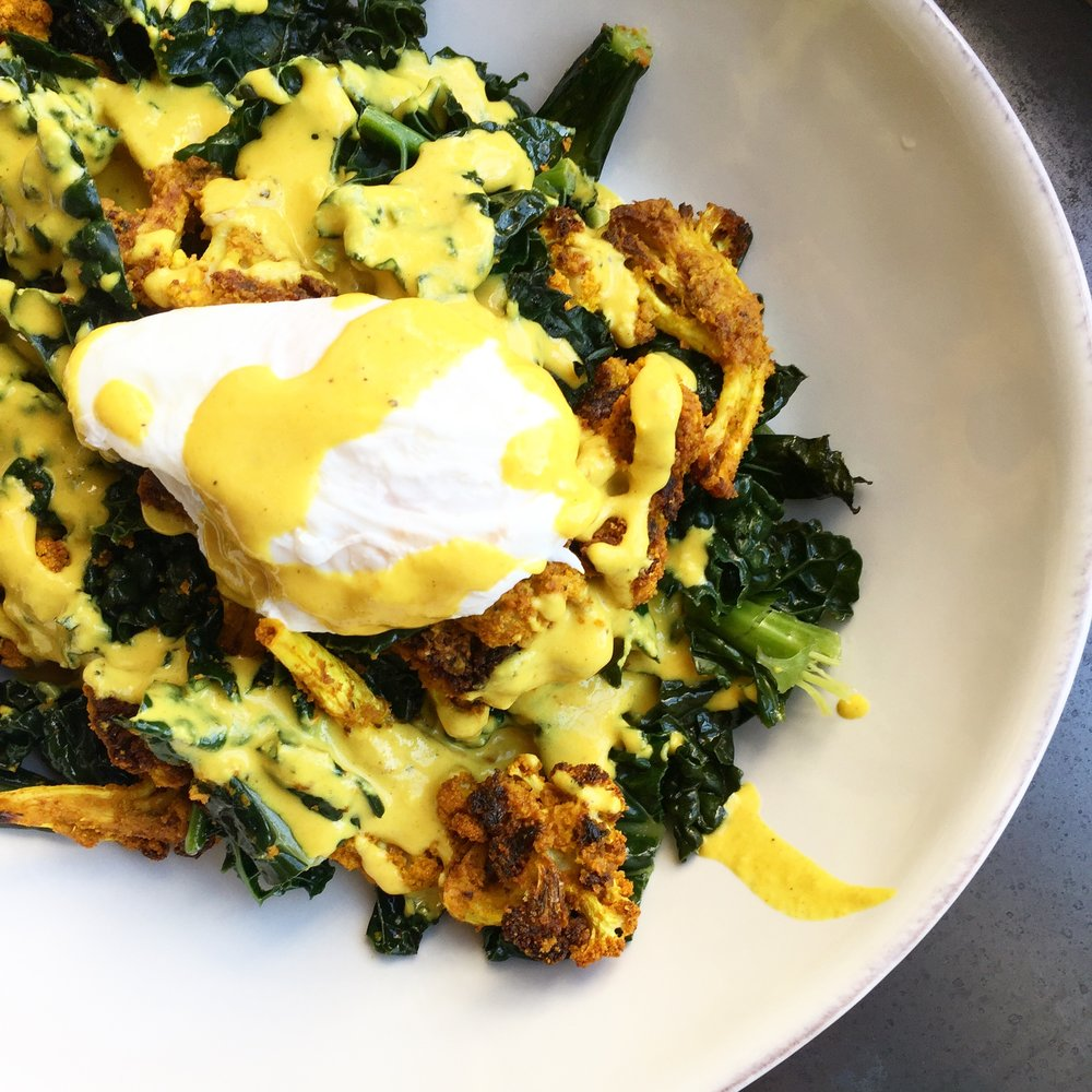 Warm kale salad with roasted cauliflower, poached egg and turmeric tahini dressing