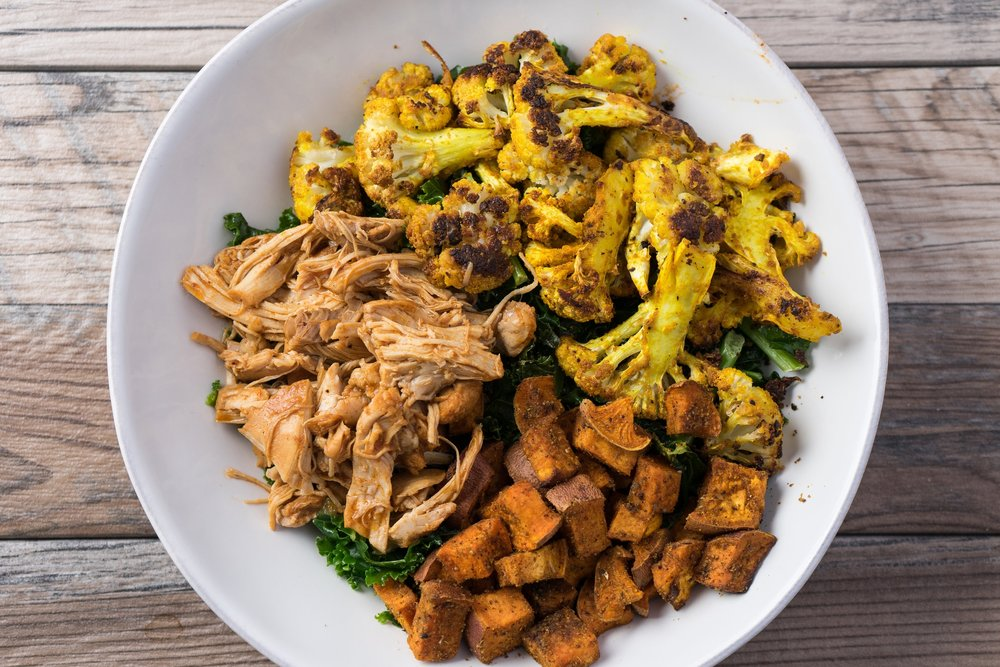 BBQ chicken bowl with roasted cauliflower, roasted sweet potatoes and steamed curly kale