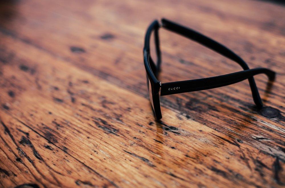 eyeglasses on wooden desk