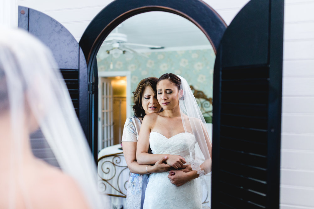 A wedding, engagement, love, newlywed image of of a bride embracing her mother-  taken by Miami Wedding Photographer, Javier Edwards of El Roi Photo, in Miami, Florida.