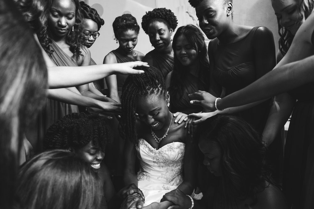 A wedding, engagement, love, newlywed image of a black bride in her wedding dress praying with her bridal party -  taken by Miami Wedding Photographer, Javier Edwards of El Roi Photo, in Miami, Florida, for a Miami Wedding