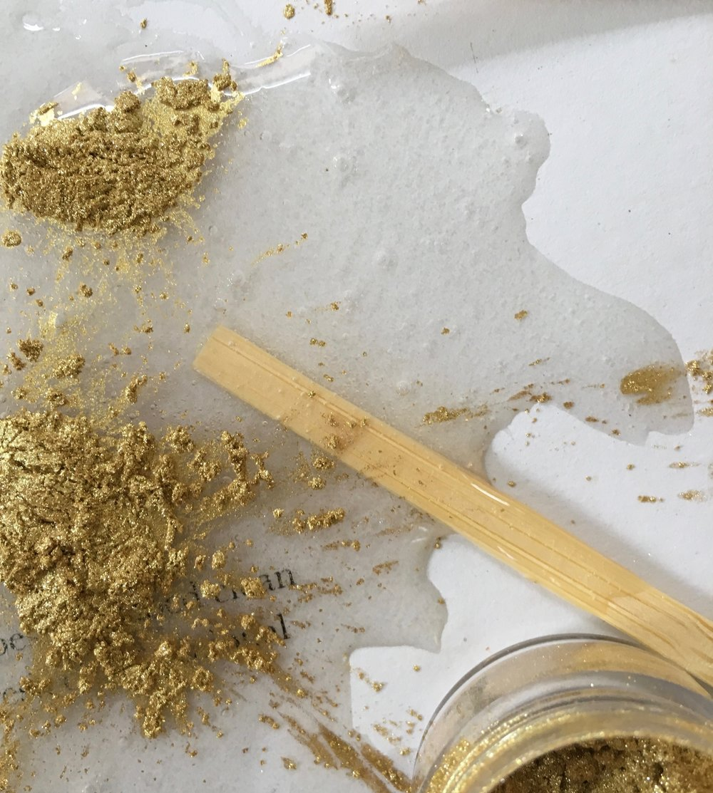 3. Stir a small amount of the gold dust into the adhesive to colour it.