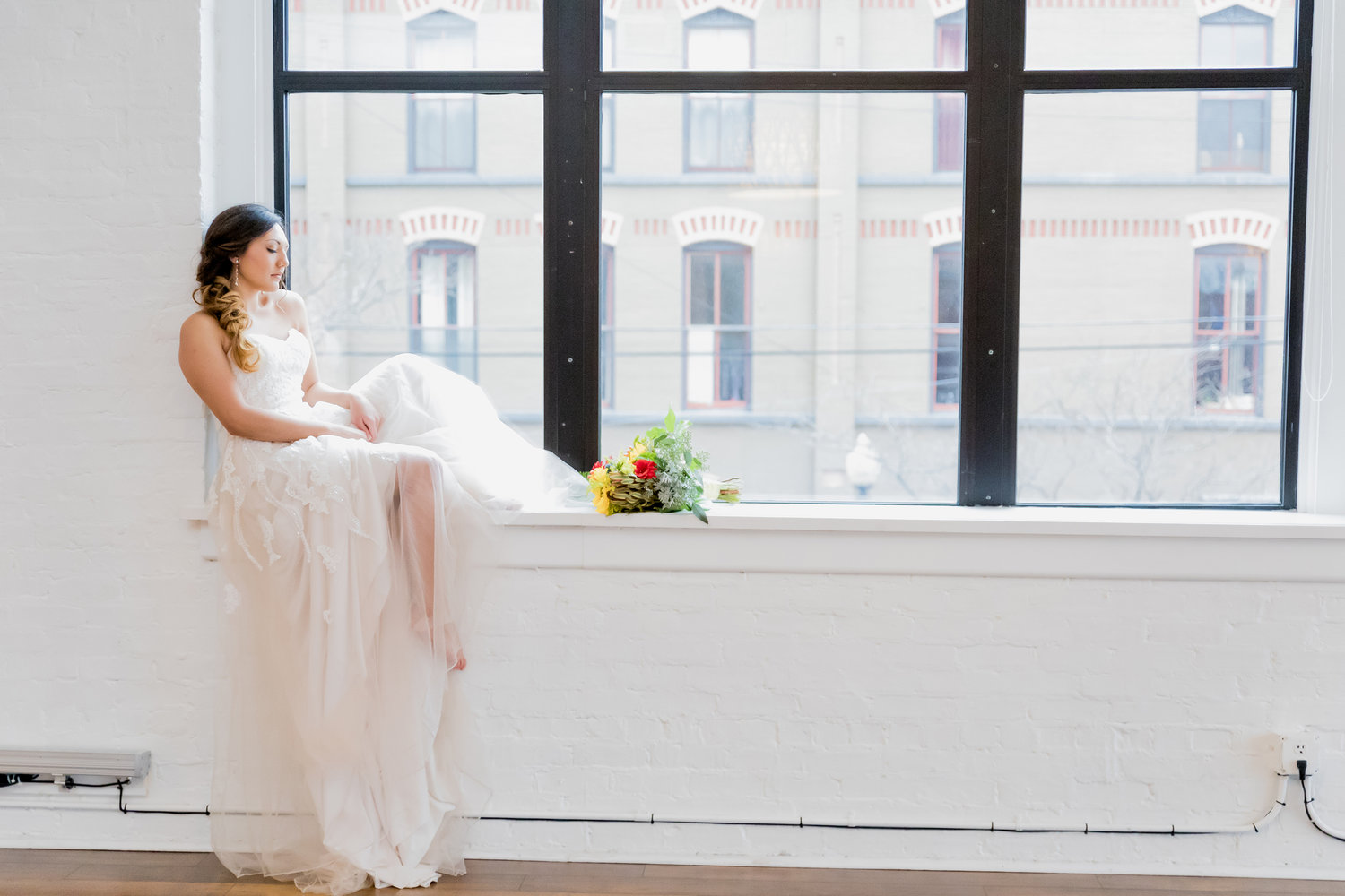 bride in gown on window sill