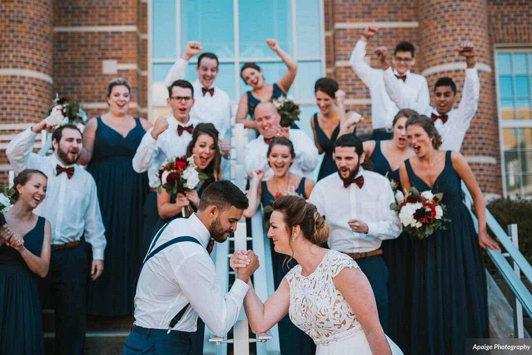 Customers of Memories wedding shop, bridal party in blue maxi bridesmaid dresses and khaki groomsmen suits.