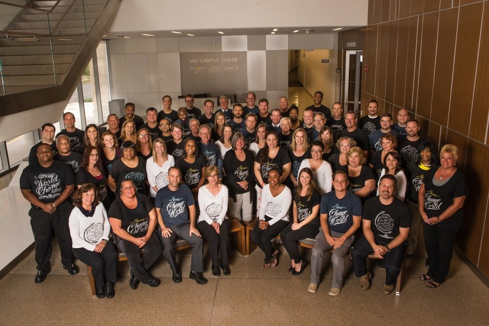 """The leadership team in the Operations & Facilities Management Department at Washington University School of Medicine poses in the Mid Campus Center while wearing Sevenly's """"Be the Change"""" t-shirts to promote employee empowerment and development."""