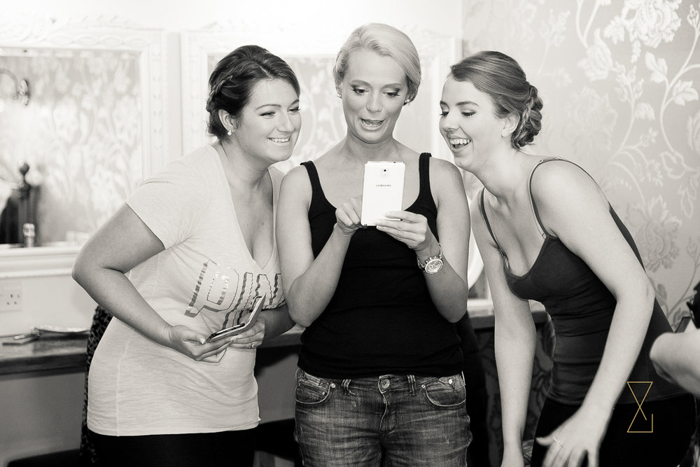 Bridesmaid reviewing a selfie at Heaton House Farm, Evans & Evans wedding photography