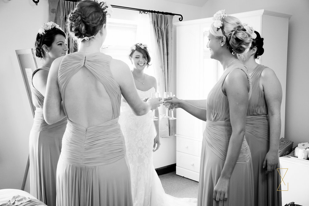 Bride and her bridesmaids sharing a toast after getting ready at Heaton House Farm, Evans & Evans wedding photography