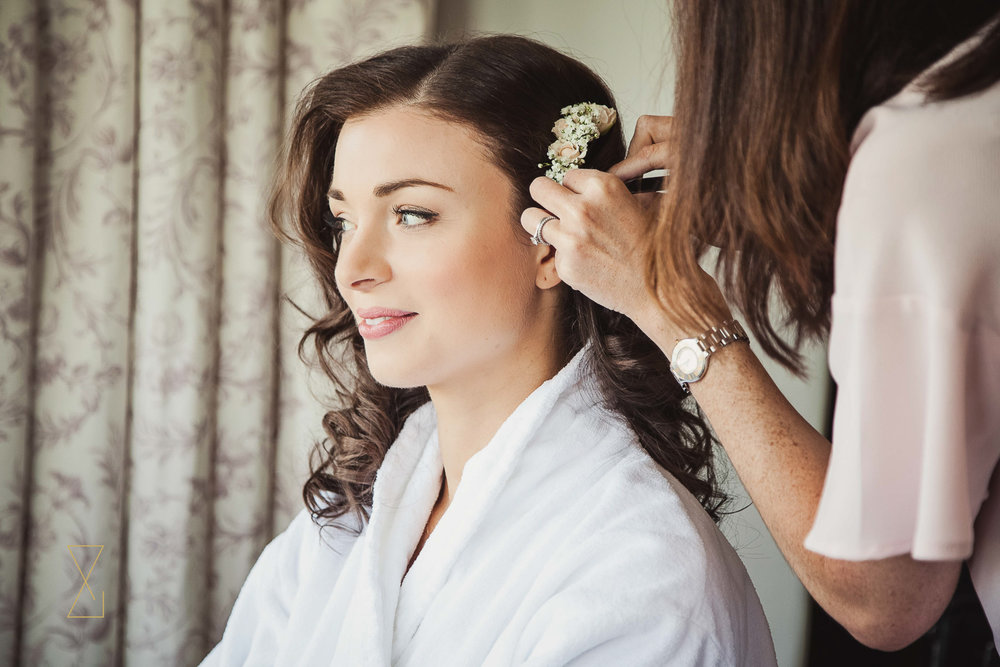 Bride having flowers put in her hair at Laura Ashley Belsfield, Evans & Evans wedding photography