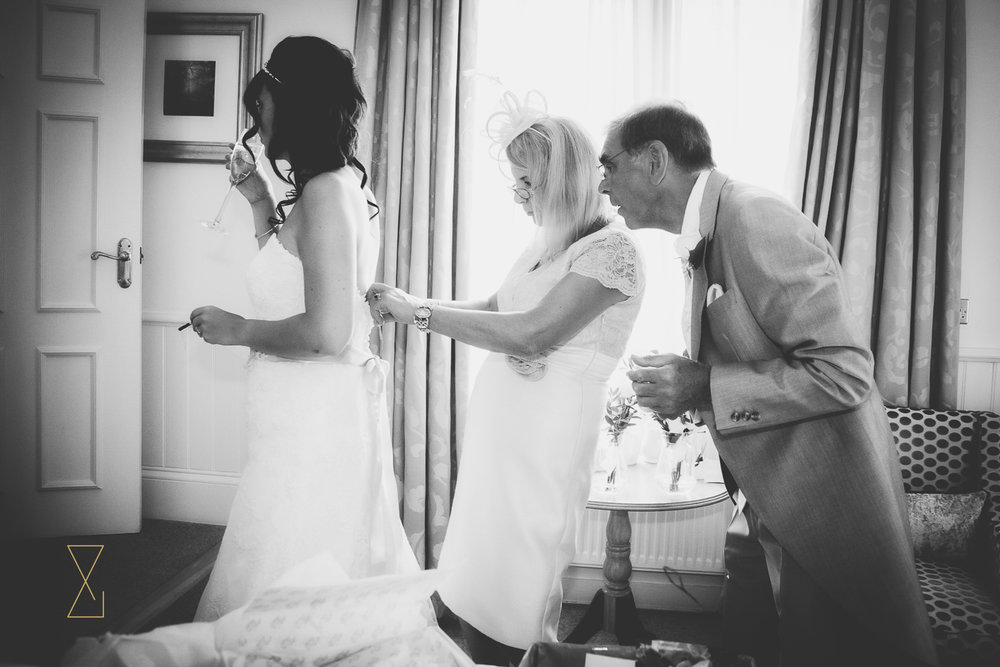 Mum and dad try to fix the dress, Evans & Evans wedding photography