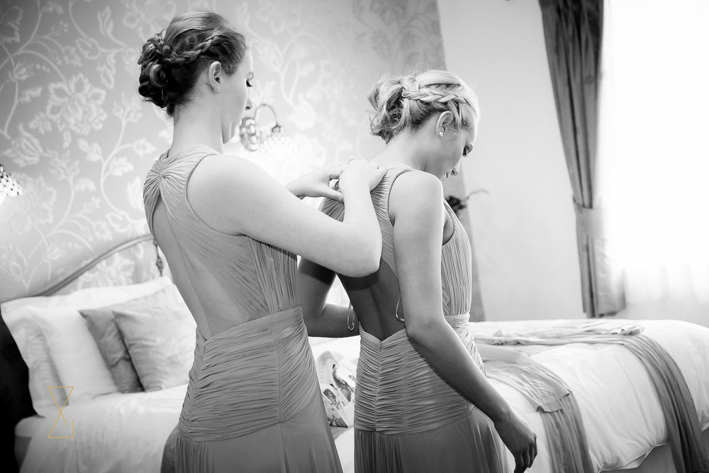 Bridesmaids helping each other into their dresses at Heaton House Farm, Evans & Evans wedding photography