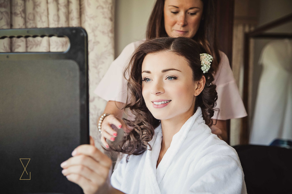 Bride admiring the work of the makeup artist at Laura Ashley Belsfield, Evans & Evans wedding photography