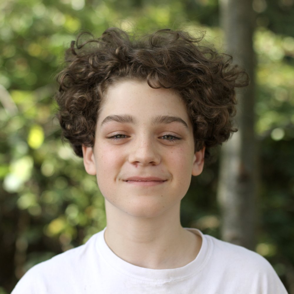 Teen boy with curly hair smiling outside at The Clearwater School.