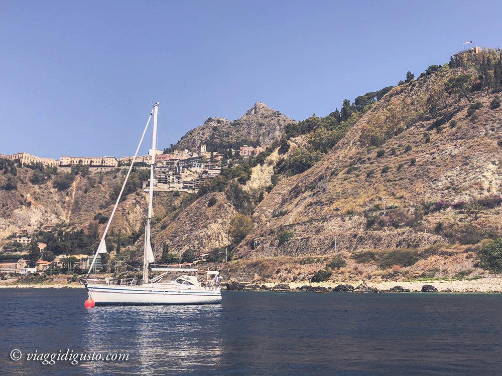 Exploring the Sicilian coastline and Isola Bella by boat.