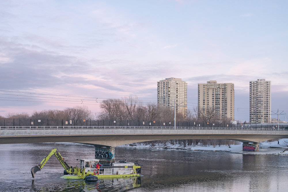 Amphibious excavation machine performing flood preventive ice breaking on Rideau River, Ottawa