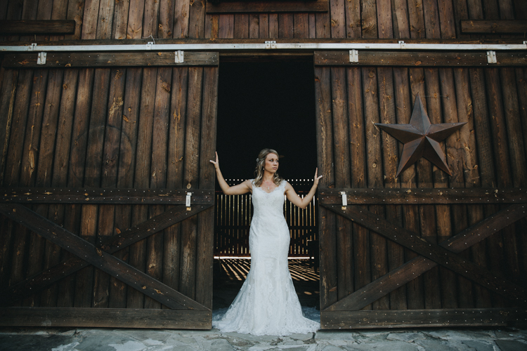 bride stands in doorway at buffalo creek venue in central north carolina