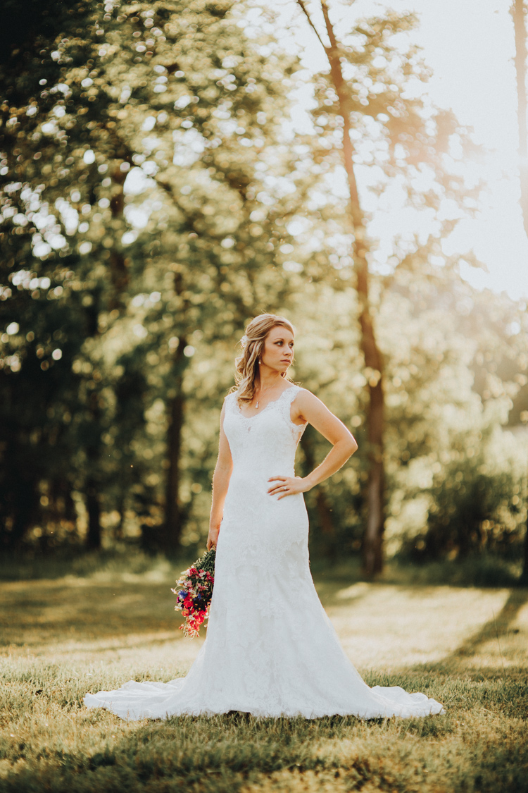 greensboro area bride in lace gown standing in open field