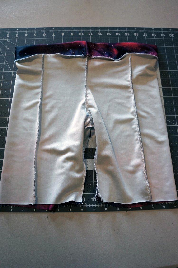Cintura cosida em shorts deixando uma pequena abertura na parte de trás.