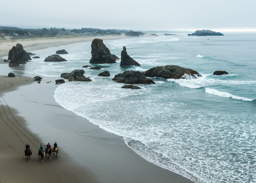 Horseback riders in BANDON, OREGON. ADOBE STOCK PHOTO.