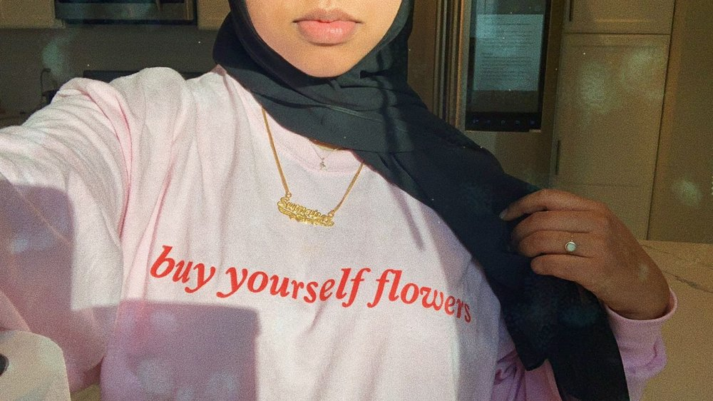 <Sumaiya wearing a pink shirt with red writing that says 'buy yourself flowers.'>      Shirt designed by @shahdbatal    (https://fanjoy.co/products/shahd-batal-buy-yourself-flowers-long-sleeve)