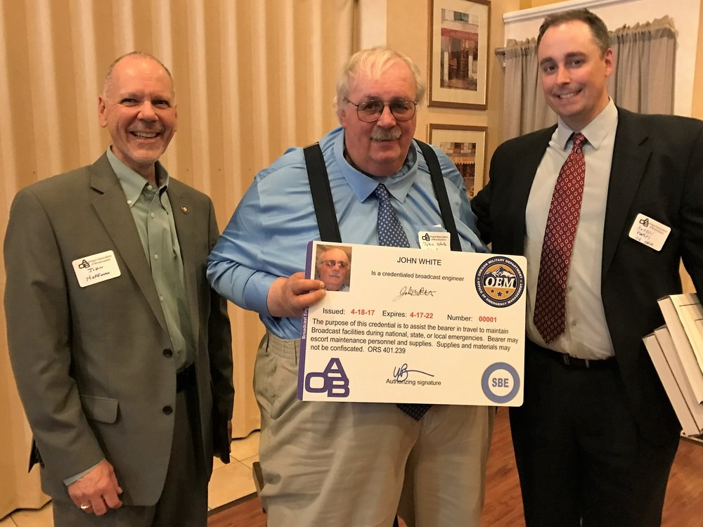Rep. John Huffman (left) and OEM Director Andrew Phelps present the initial First Informer credential to broadcast engineer John White (center) at the 2017 OAB Day at the Capitol Legislative Reception.  Rep. Huffman was the prime sponsor of HB 2210, which created First Informers in the state of Oregon.