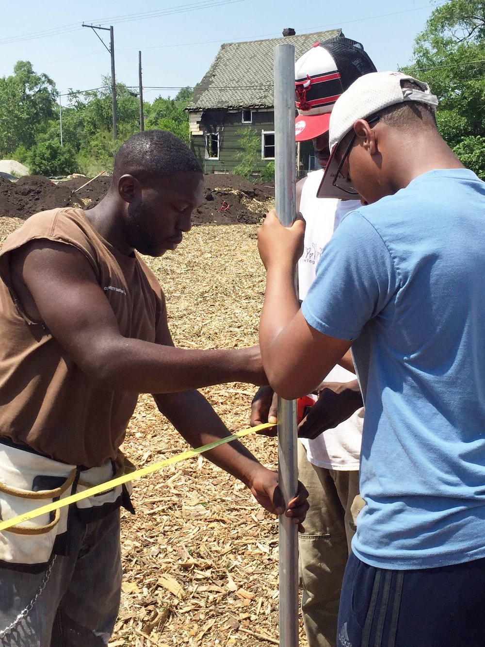 Growing Power staff and community volunteer work together to install posts