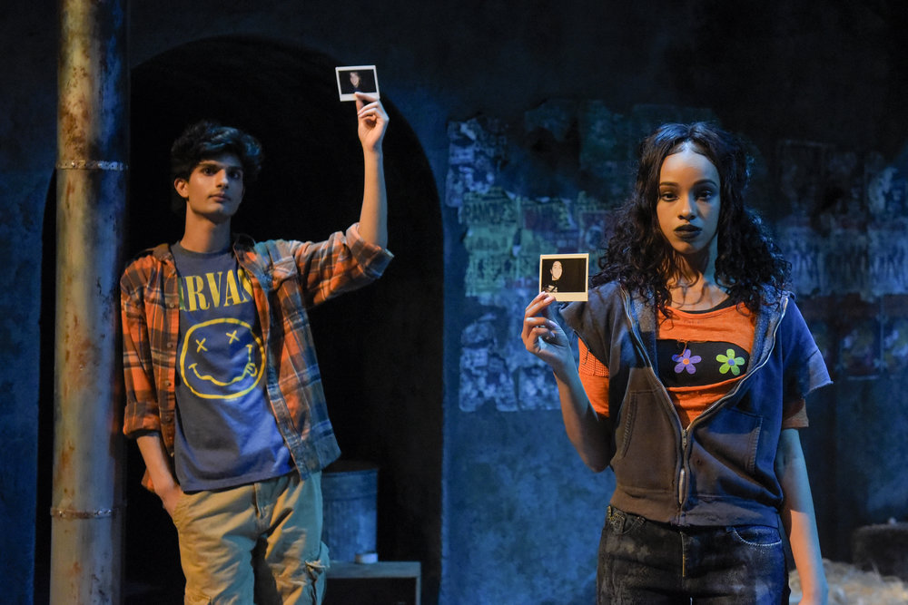 Orpheus (Yohana Ansari-Thomas) and an ensemble cast member (Farryl Lawon) hold up photographs of some of the real street youth whose interviews with playwright Naomi Iizuka inspired  Polaroid Stories . Photo: Alessandra Mello.