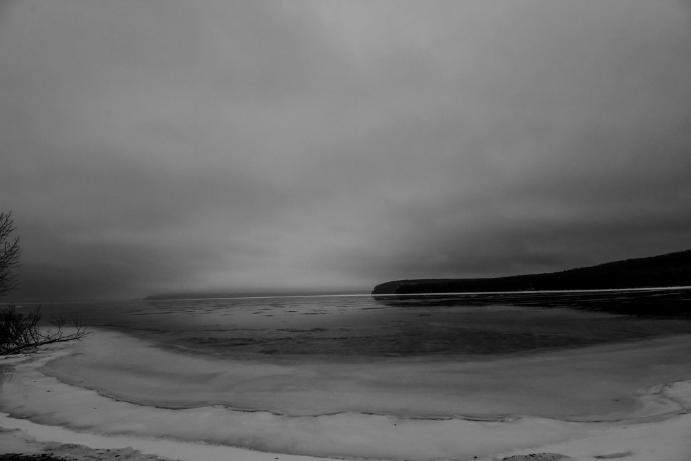 Oppressive fog and heavy cloud-cover dominate the somber winter skyscape over Nicolet Bay.