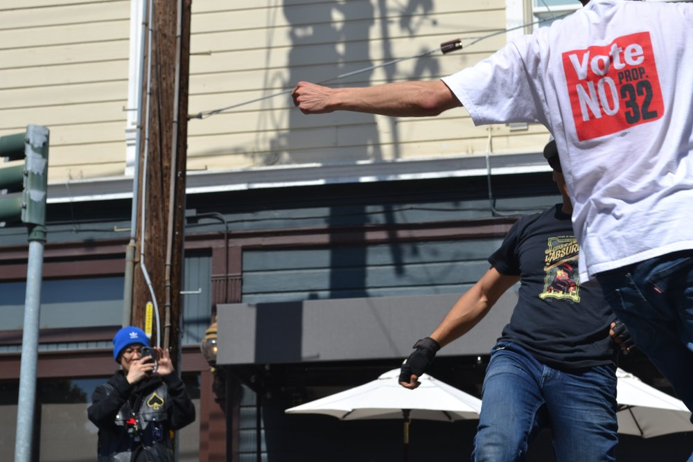 Sunday Streets Mission District 3/11/2018 . A man breakdancing in part of a non profit hip hop group that teaches children to dance. In retrospect, I noticed how his clenched fist at the center; a historical symbol of solidarity, support and defiance, he stands in support of California Proposition 32.