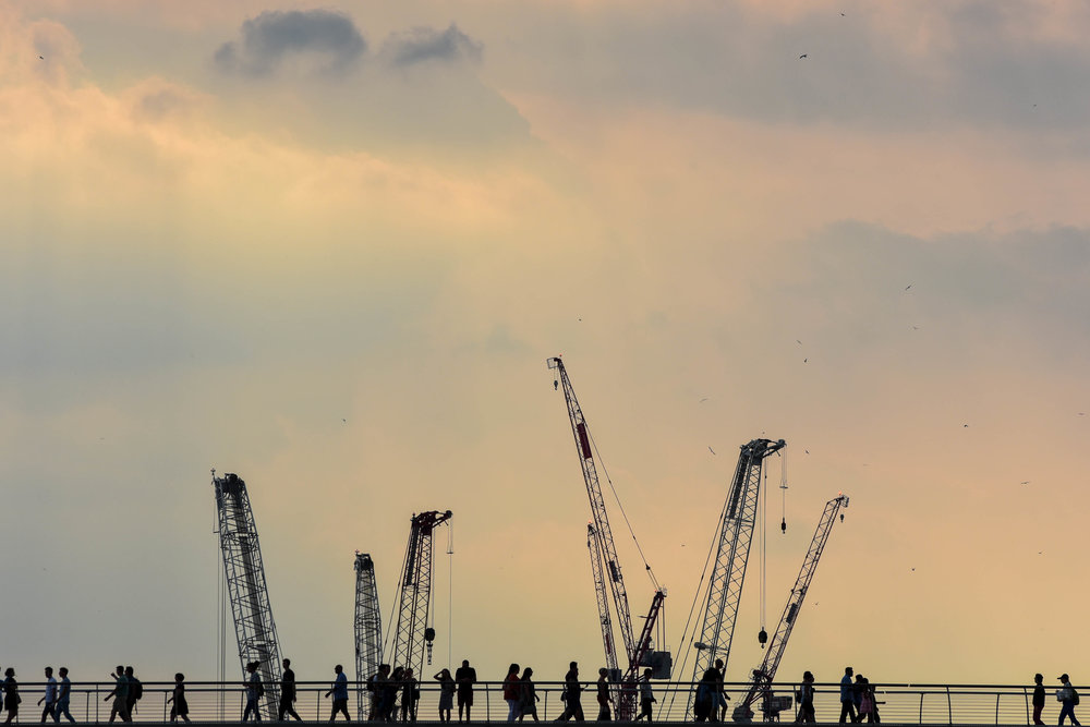 Pedestrians crossing a bridge over London's River Thames are silhouetted against a moody afternoon sky, as construction cranes loom on the horizon.