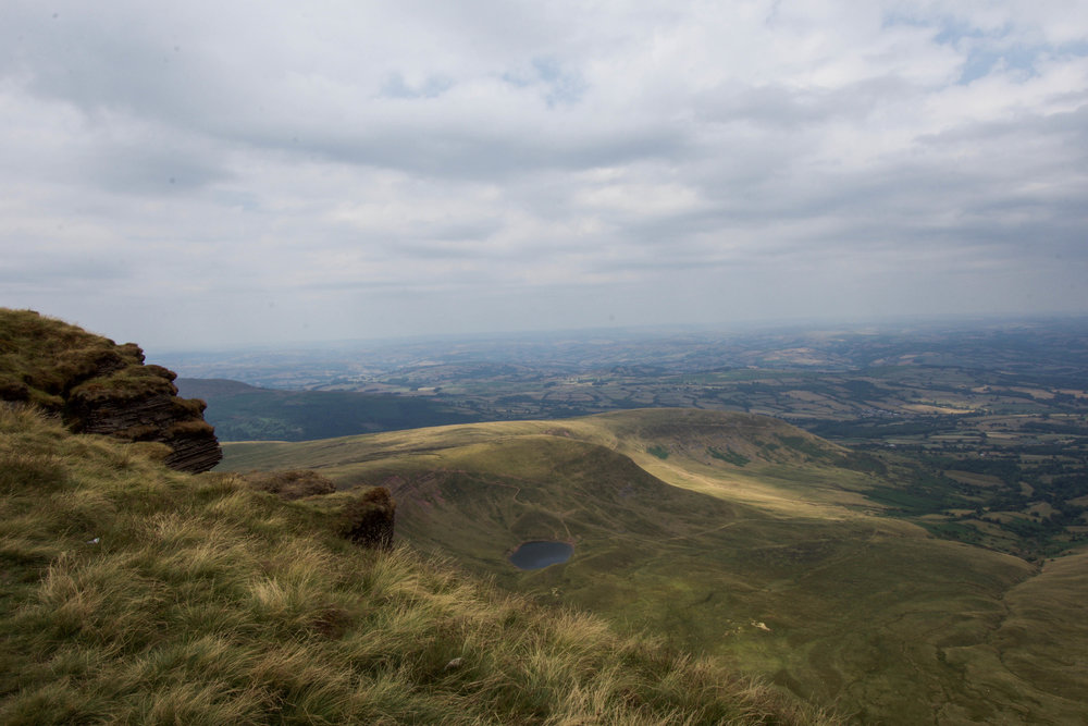A view of the expansive green plains of Brecon Beacons National Park from atop Pen Y Fan, the tallest peak in the pastoral region of South Wales.
