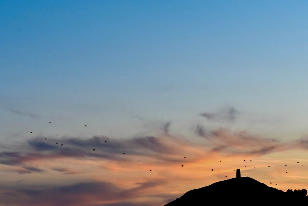 The Glastonbury Tor, an important spiritual site in Christianity, Celtic mythology, and new-age Goddess Worship, is silhouetted against the vibrant evening sky.