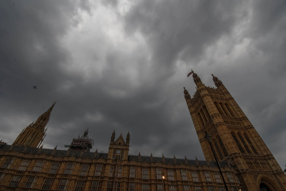 The Palace of Westminster, home of the UK's houses of Parliament, is set against an overcast evening sky.