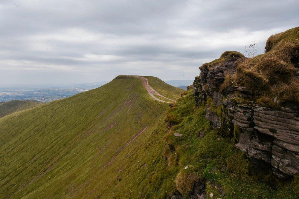 A rocky outcrop atop the emerald slopes of Brecon Beacons.