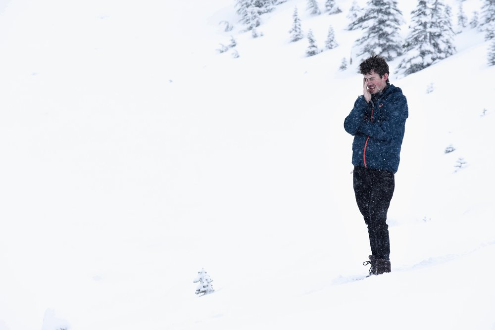 Fresh snow began to fall as we traversed the mountain's slopes, catching my friend by surprise.