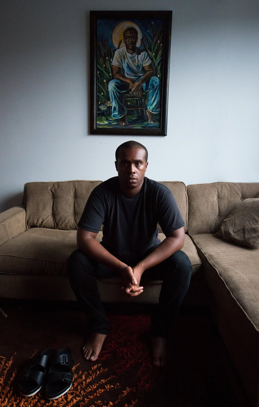 Jermaine T. Bell sitting underneath a painting by  Stephen Towns . Image by  Rob Ferrell .