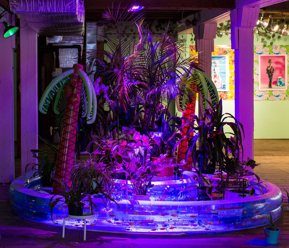 "Tiffany Smith, ""Decolonized Fountain of Fleeting Youth"", Inflatable pool and palm trees, live and artificial plants, plant stands, floating led flowers, decorative plastic sheeting, grow lights, water"