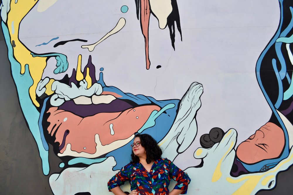 Image:  Michelle Ivette Gomez, Founder of Creative Unions Event Design LLC in front of a mural by artist, Jose Mertz