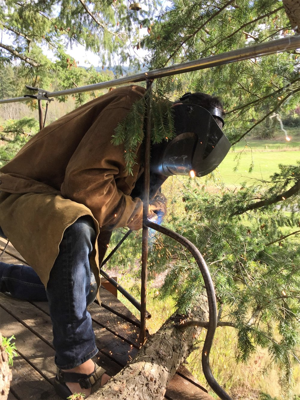 Alexei Ford welding railing at three-story sculptural tree fort.JPG