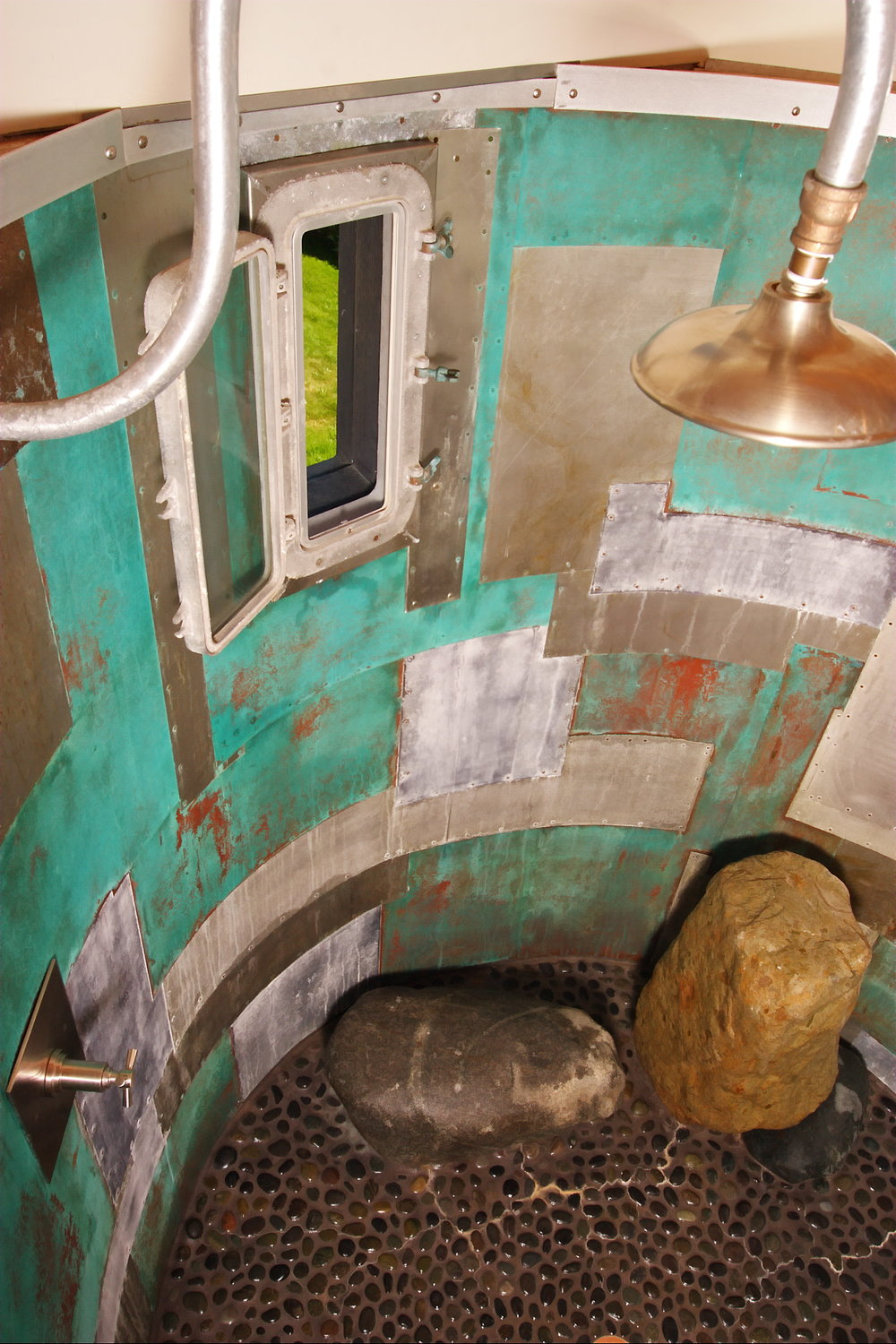 oxidized metal patchwork shower with porthole window to outdoors and natural stone.jpg