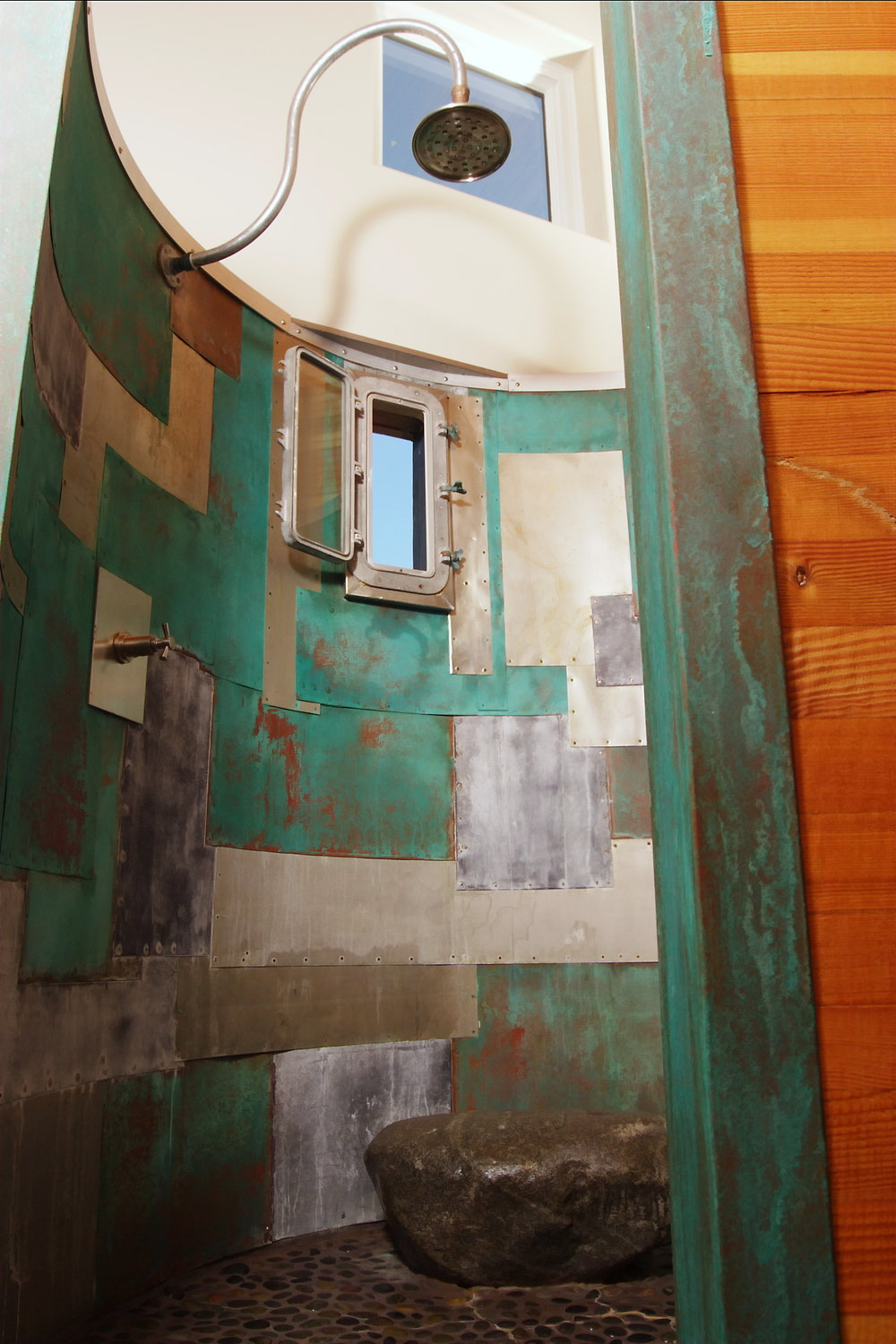 oxidized metal patchwork shower with porthole window to outdoors seating.jpg