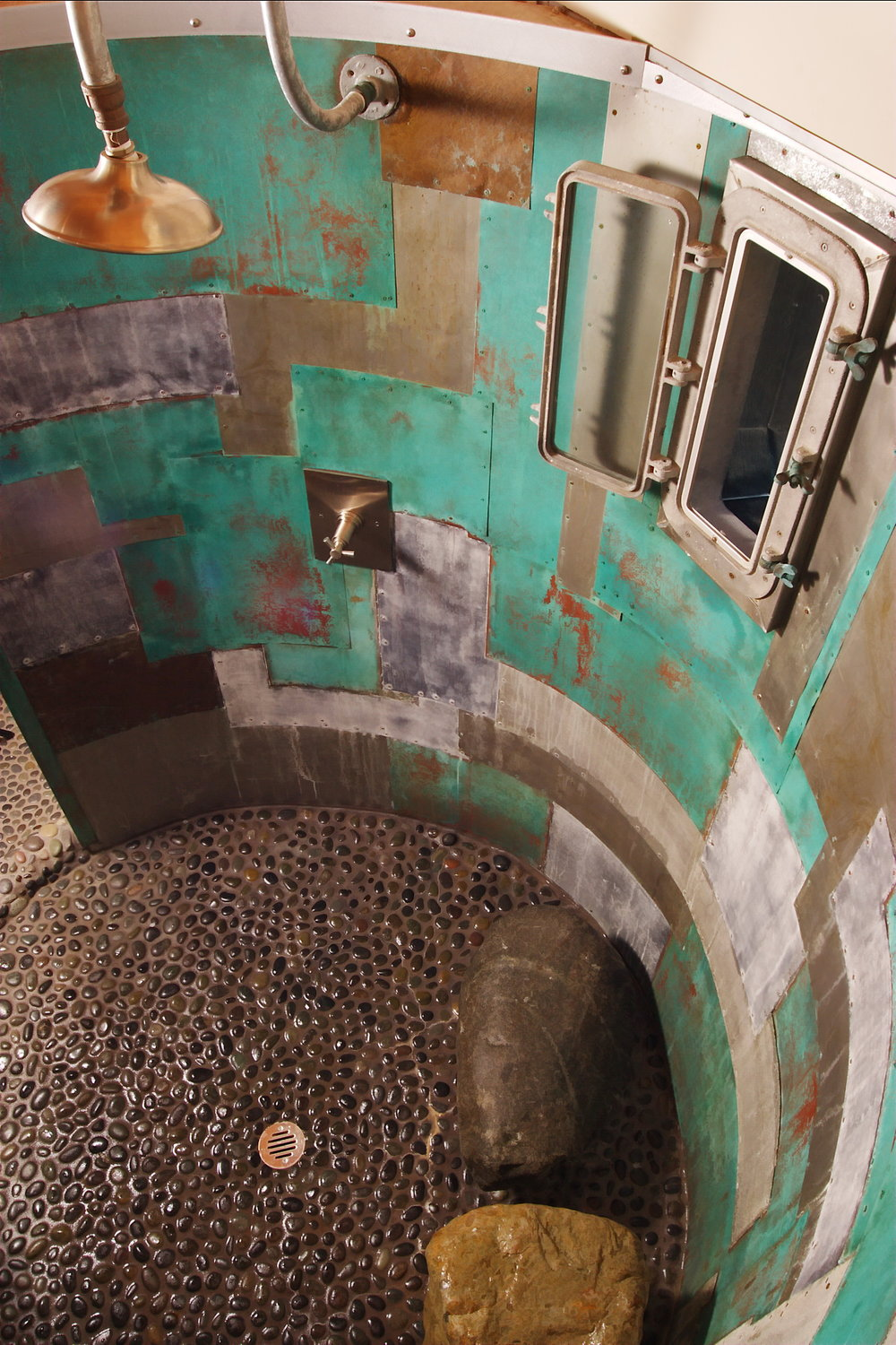 oxidized metal patchwork shower with rectangular porthole window and natural stone seating.jpg