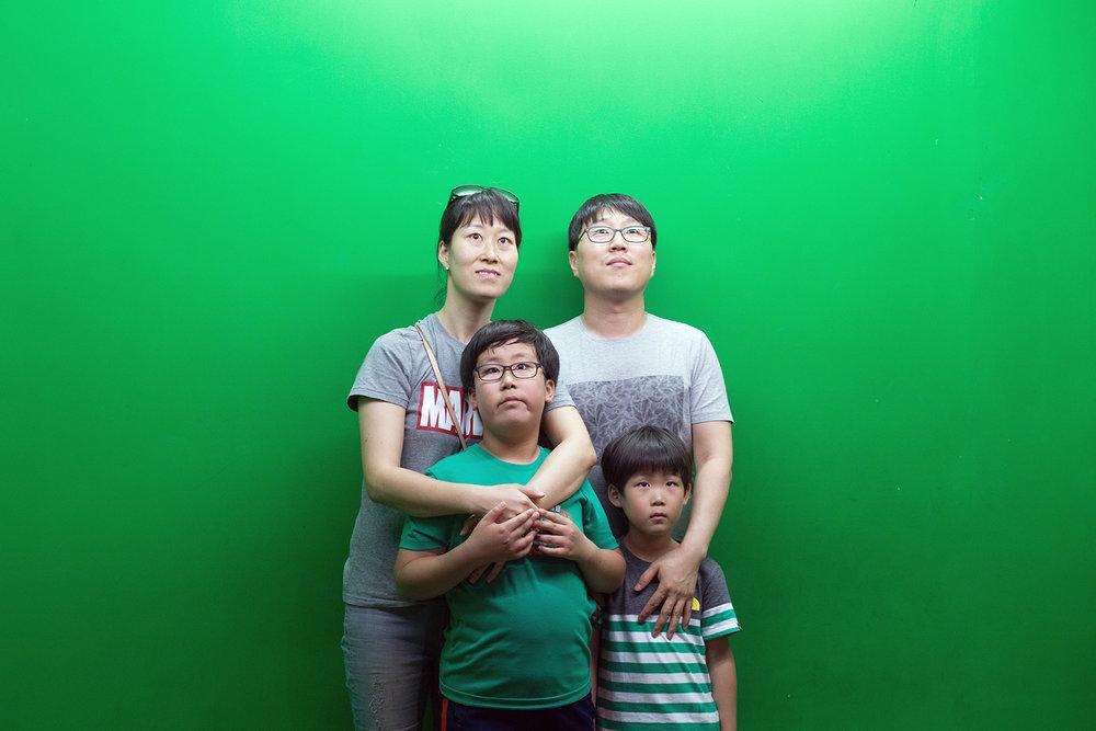 Una famiglia aspetta di essere fotografata su un green screen a cui verrà aggiunto un paesaggio marino, all'Acquario della città portuale Busan (nella punta sud-est della Penisola). Dalla serie Made in Korea. © Filippo Venturi.