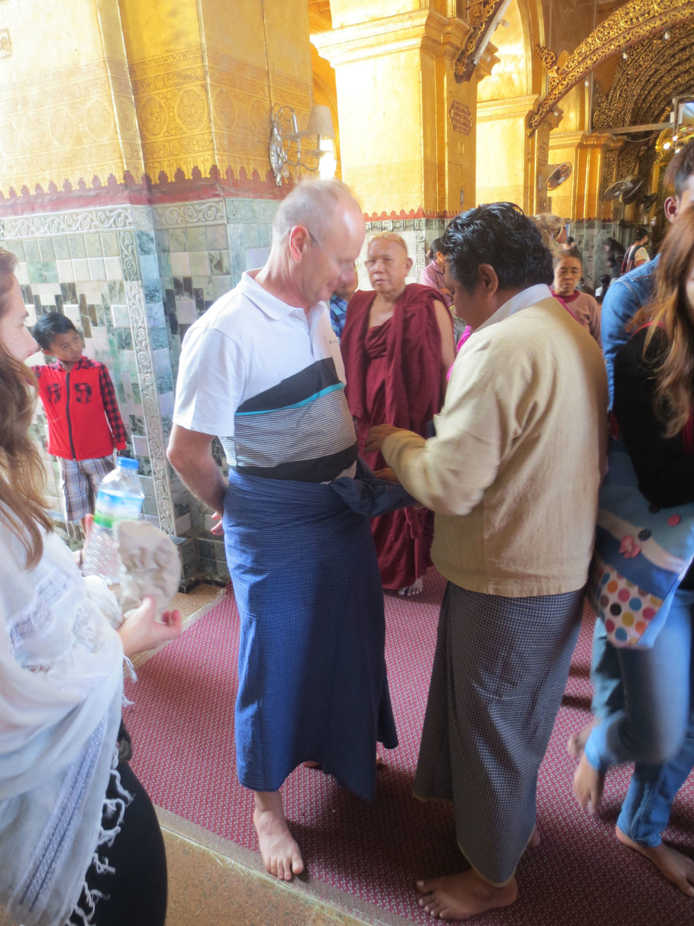 Fitting a Longyi before entering a temple