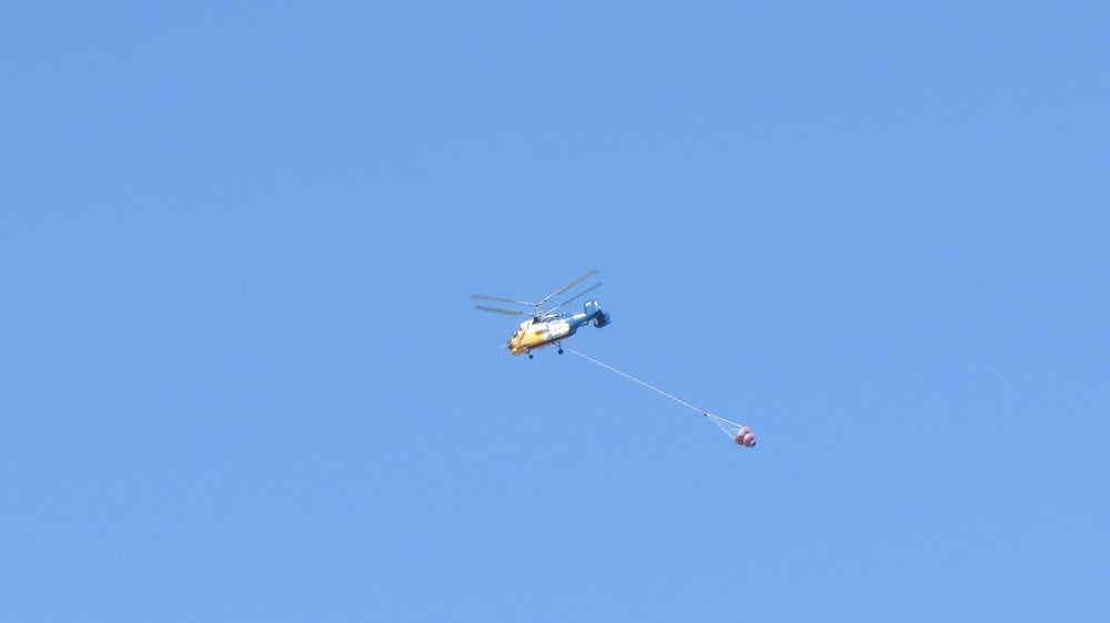 Firefighting helicopter on route to yet another fire in the mountains. The water container was filled with seawater and will be dumped on the fires raging in remote area's.