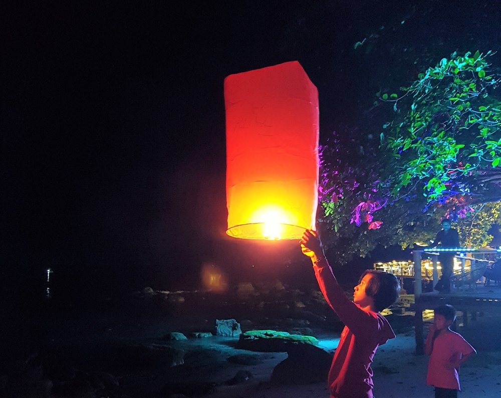 Local boy launching a Chinese flying lantern