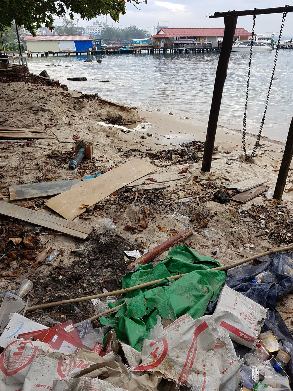 Trash on the beaches with Sihanoukville pier in the background