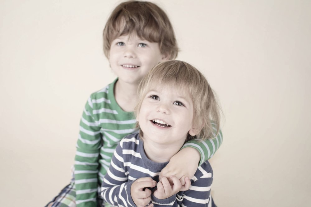 Young boys in stripy tops smiling after children's dentistry